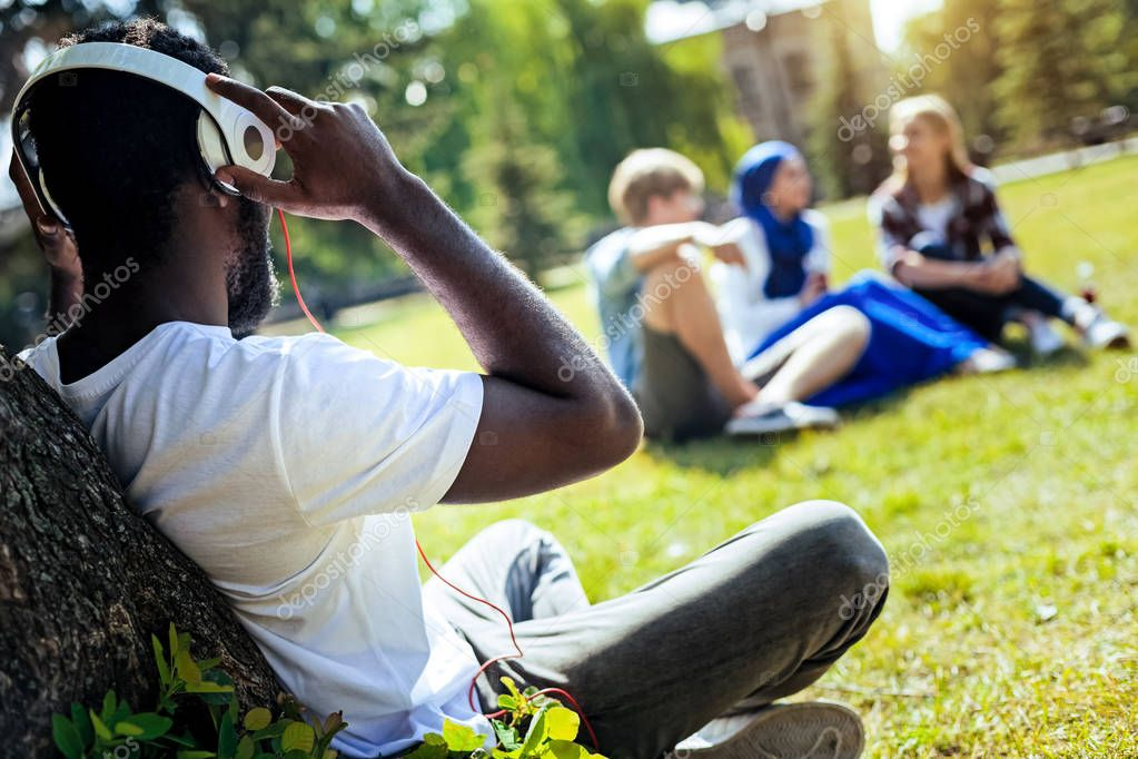 Relaxed young man listening to music outdoors