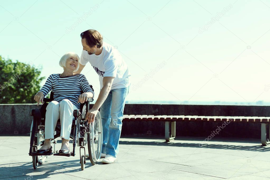 Kind volunteer helping disabled woman
