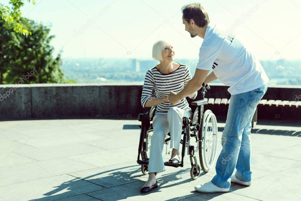 Joyful blonde holding hands of social worker
