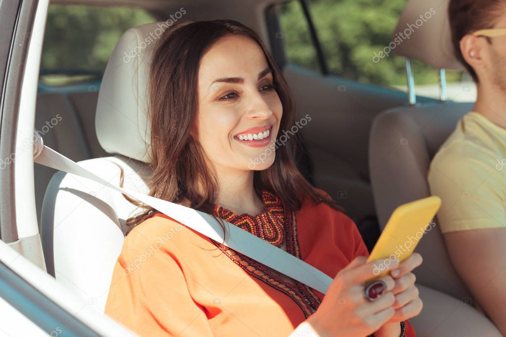Dark-haired woman texting her friend while sitting in car near her man