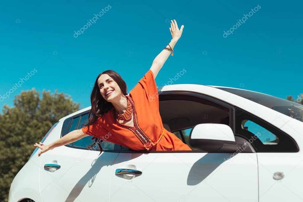 Smiling beautiful woman feeling free while traveling in car