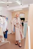 Stylový zralá žena stojící poblíž velké zrcadlo v showroomu