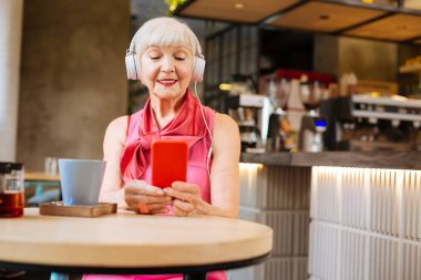 Happy aged woman wearing headphones