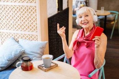Cheerful elderly woman enjoying the song