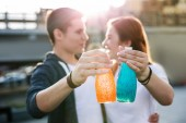 Bottles with drinks being in hands of joyful young people
