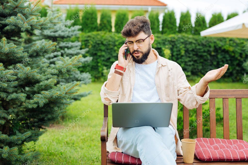 Bearded freelancer arguing with his colleague on the phone