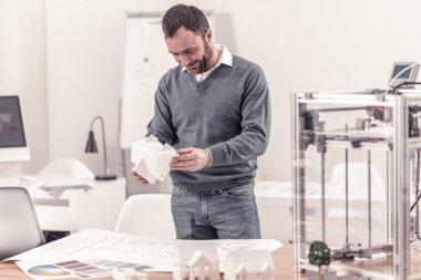 Ingenious designer holding model of a house