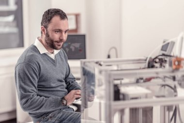 Pleasant adult man watching at 3D printer