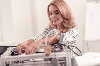 Pretty adult smiling woman adjusting 3D printer