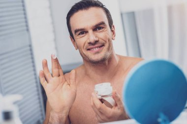 Smiling muscleman using face cream