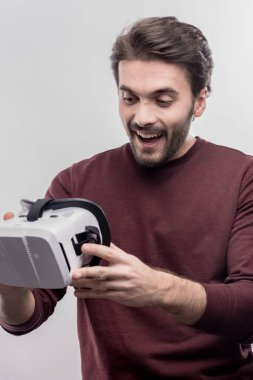Great fan of video games holding virtual reality glasses in hands