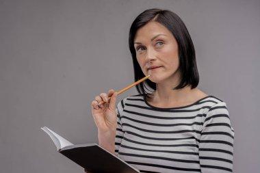 Dark-haired chemistry teacher feeling busy while composing final test