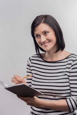 Smiling pleasant artist drawing sketches in her black notebook