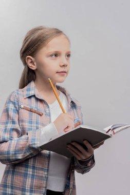Smart good-looking blonde-haired schoolgirl doing her homework