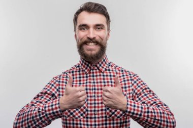 Beaming bearded dark-haired office manager feeling satisfied and cheerful