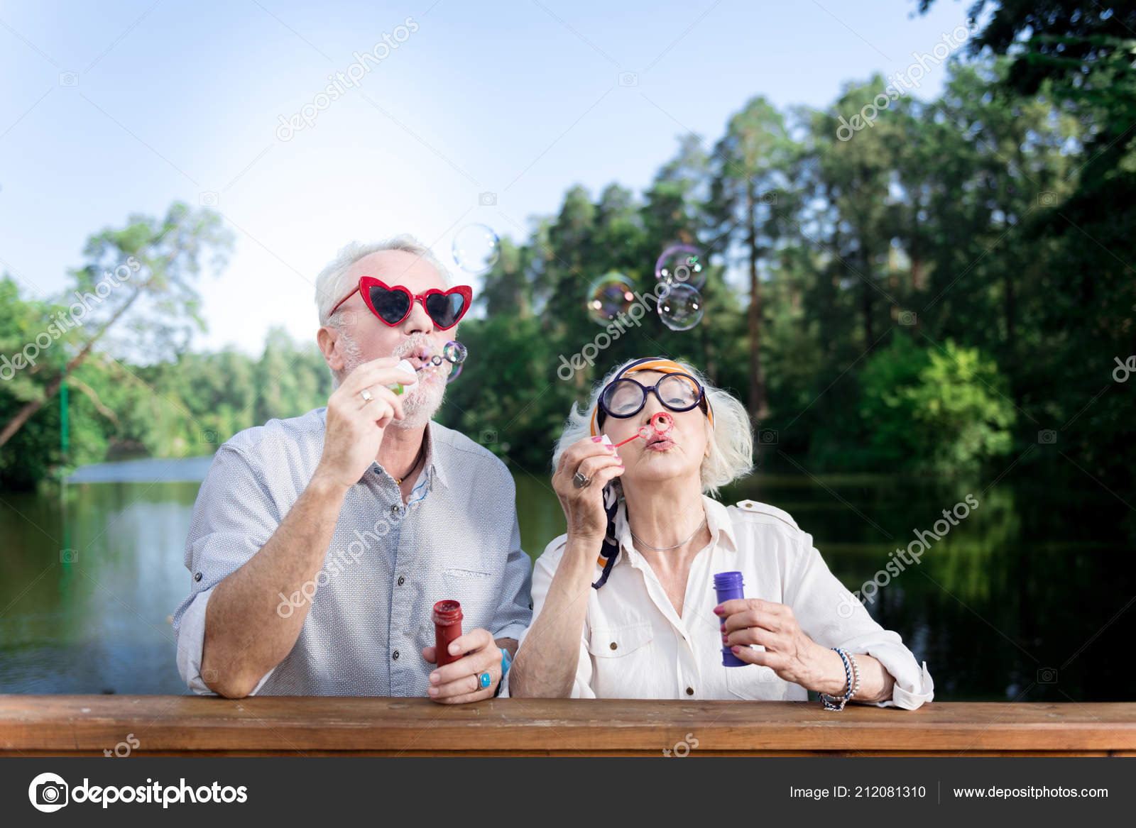 9ecd7f6f29d Red sunglasses. Funny elderly man wearing red heart shape sunglasses using  soap bubbles standing near his wife — Photo by ...