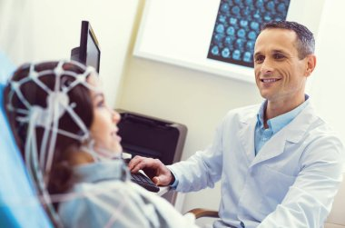 Friendly looking doctor smiling while conducting electroencephalography analysis