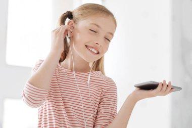 Relaxed kid enjoying her playlist