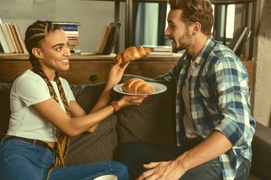Mindful young lady treating soulmate with tasty pastry