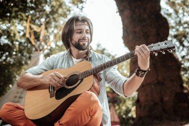 Smiling bearded man singing songs playing guitar