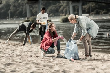 Loving responsible mother volunteering on the beach with her three children