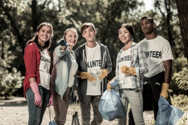 Active young volunteers holding garbage bags with trash after cleaning up the forest