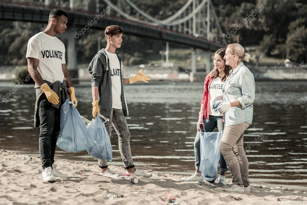 Three active volunteers talking to their team leader after cleaning the beach