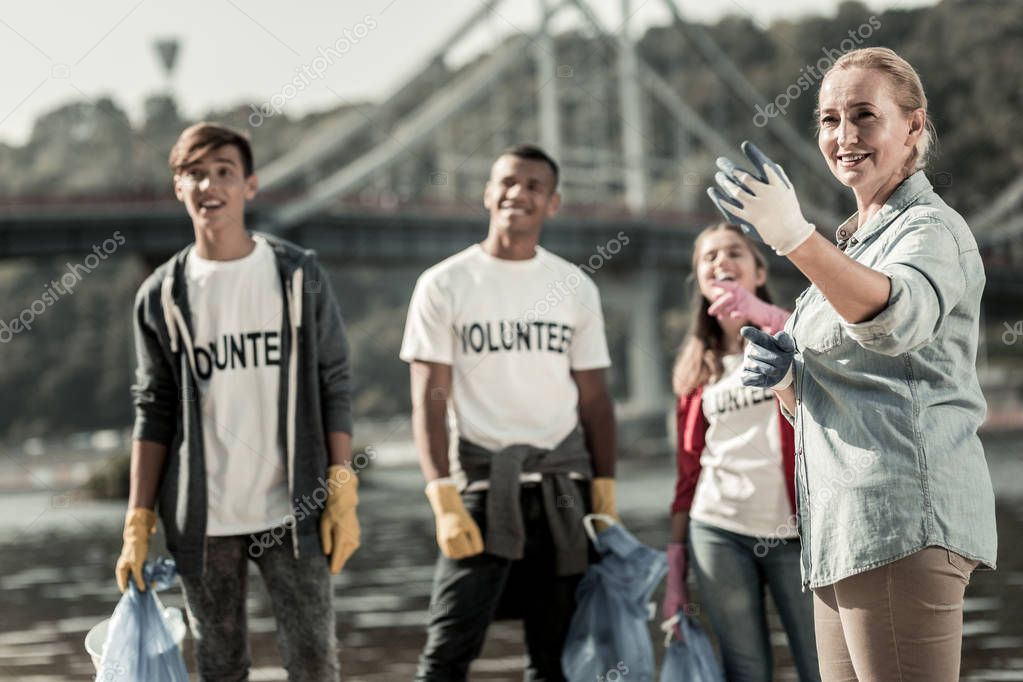 Company of team leader and three young volunteers cleaning up the beach