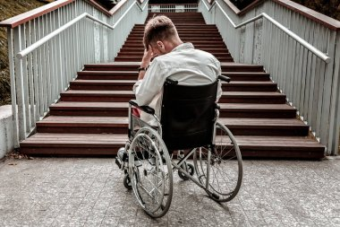 Laconic image of disabled man sitting in front of the stairs