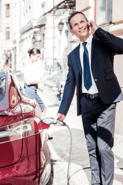 Handsome businessman standing near his auto