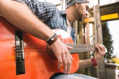 Budding male guitarist enumerating stings on guitar