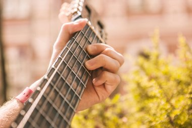 Young male hands oppressing string against frets