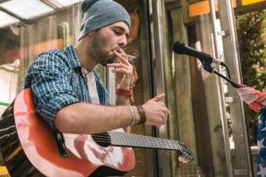 Focused male guitarist lighting cigarette on street