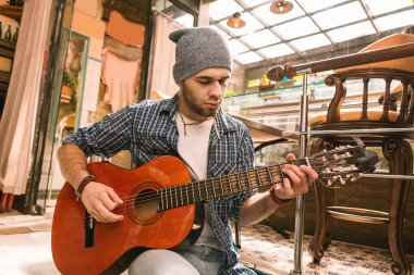 Pensive male guitarist practicing song in bar