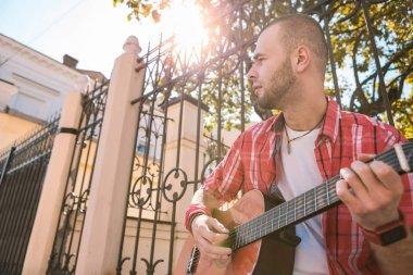 Appealing street musician reaching aim in music
