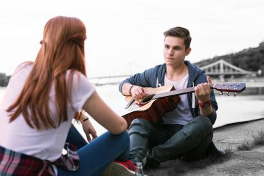 Handsome boy singing the song for his girlfriend sitting near the bridge