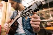 Pozorný muž kytarista úprava kytaru před přehráváním