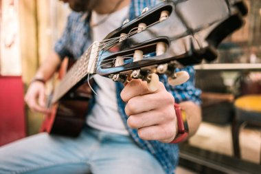 Determined male guitarist tuning guitar for playing