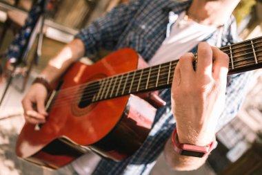 Male young guitarist selecting proper guitars practice