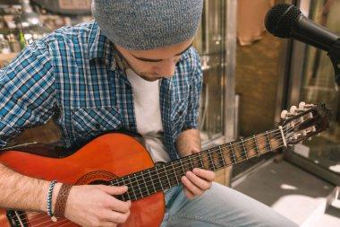 Attentive male guitarist struggling for perfect technique