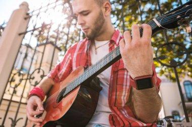 Handsome street musician making progress in music