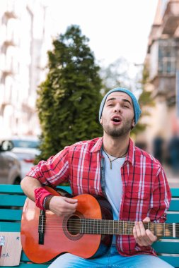 Open minded street musician voicing emotions through song