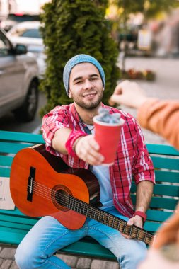 Charming male guitarist getting coins for music