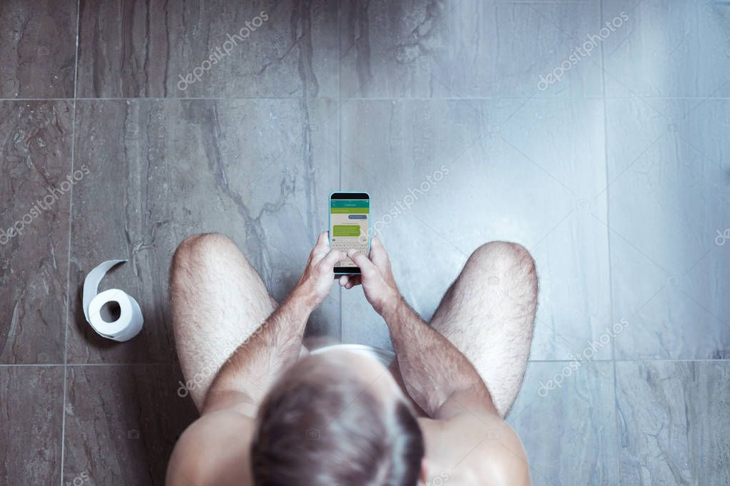 Blonde-haired man holding his smartphone while sitting in the toilet