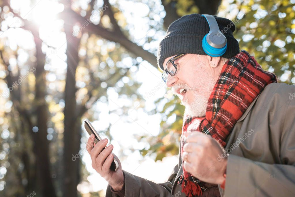 Pleasant senior man listening to his favourite song