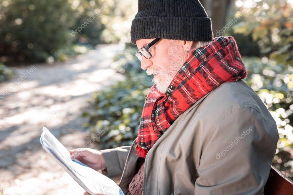 Smart intelligent man reading different newspaper articles