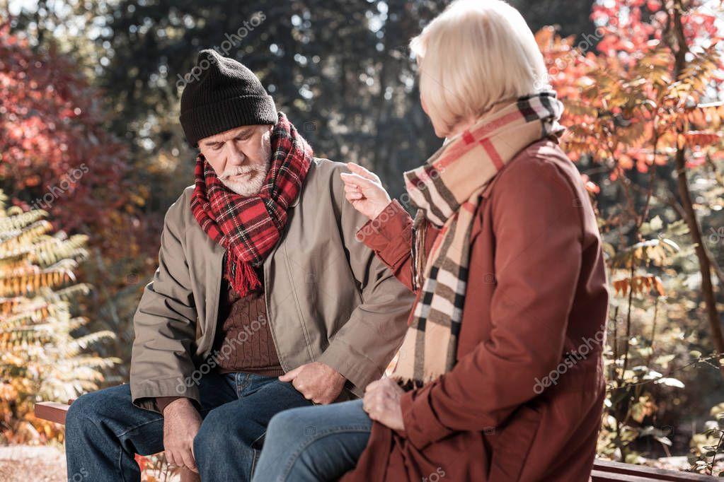 Depressed sad man listening to his wife