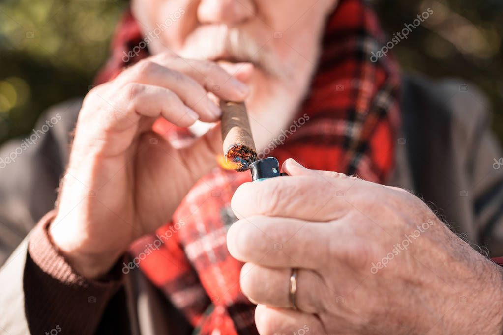 Selective focus of a cuban cigar being lit