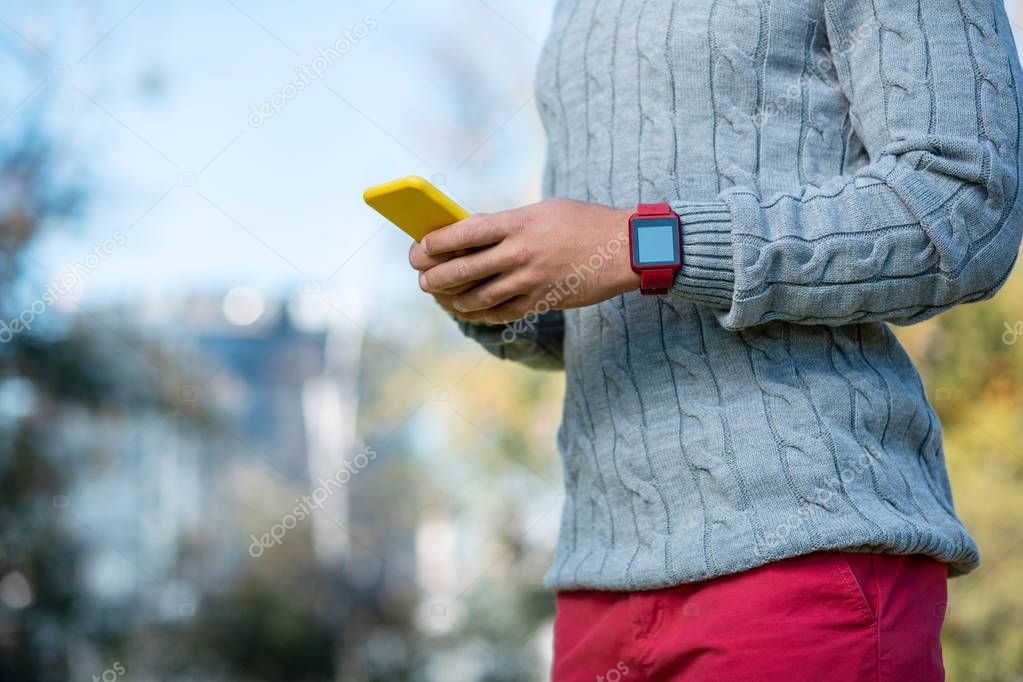 Stylish young man demonstrating his smart watches