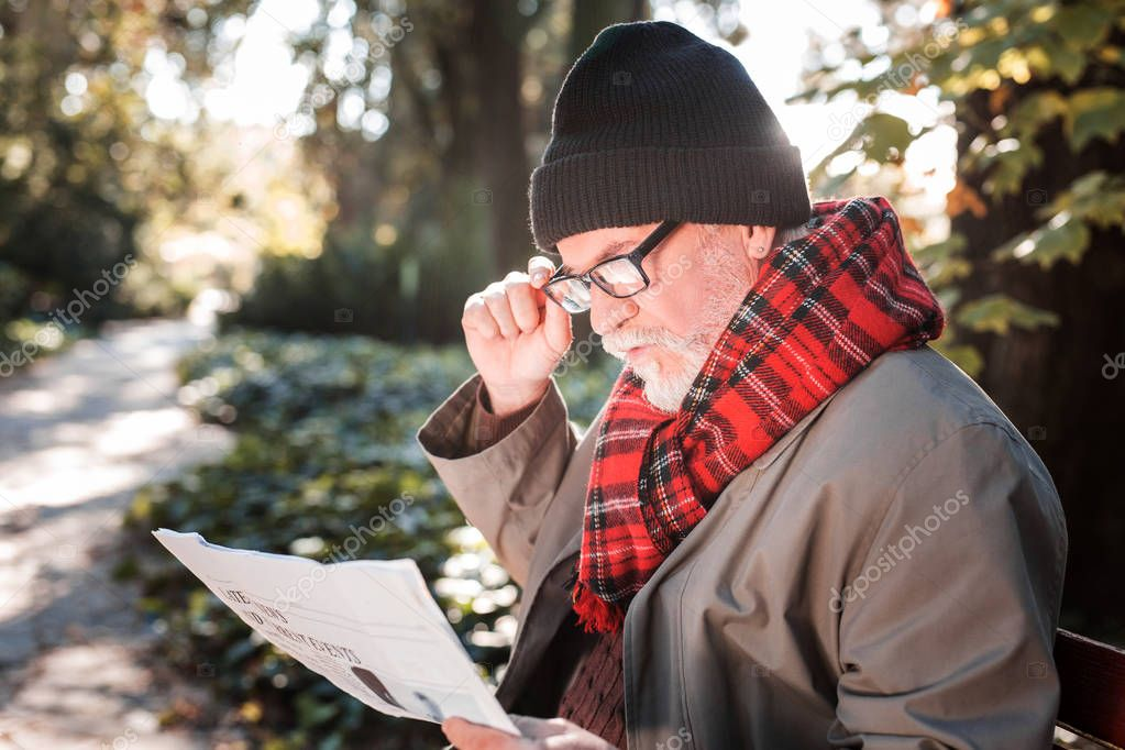 Smart aged man reading a morning newspaper